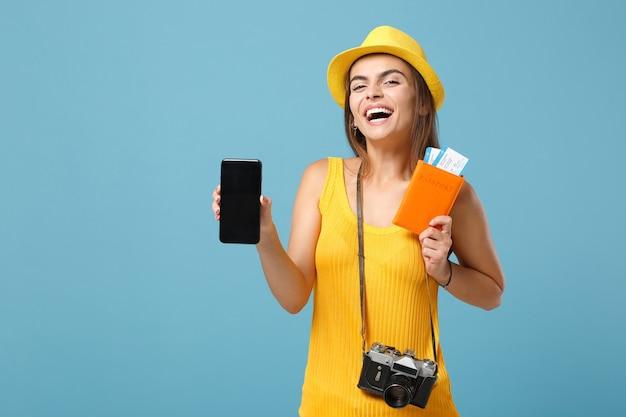 Podróżnik turysta kobieta w żółtym kapeluszu na co dzień trzymający bilety telefon komórkowy aparat na niebiesko