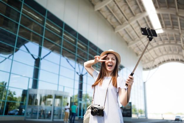Podróżnik turysta kobieta z retro vintage aparatem fotograficznym pokazuje znak zwycięstwa, robi selfie na telefonie komórkowym z samolubnym kijem monopod na lotnisku