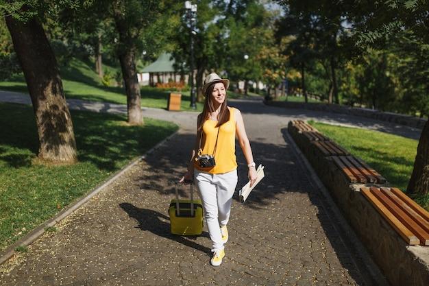 Podróżnik turystyczny kobieta w żółtym letnim ubraniu i kapeluszu z walizką, mapa miasta spacerująca po mieście na świeżym powietrzu. dziewczyna wyjeżdża za granicę na weekendowy wypad. koncepcja życia podróż turystyka.