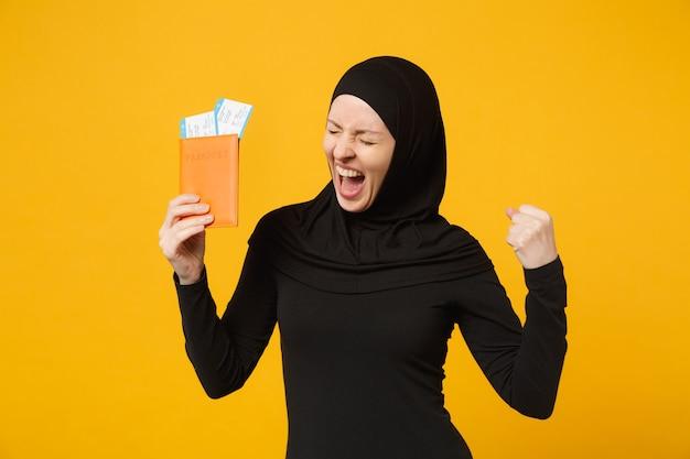 Podróżnik turystyczny młoda arabska muzułmańska kobieta w hidżab czarne ubrania posiadają bilety paszportowe na białym tle na żółtą ścianę portret. koncepcja życia religijnego ludzi.