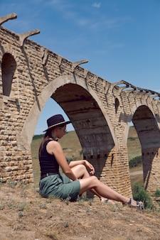 Podróżnik w czarnym kapeluszu siedzi latem obok zniszczonego starego kamiennego mostu