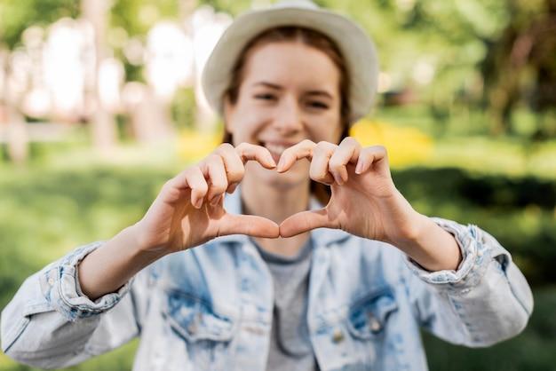 Podróżnik w parku robi kształtowi serce