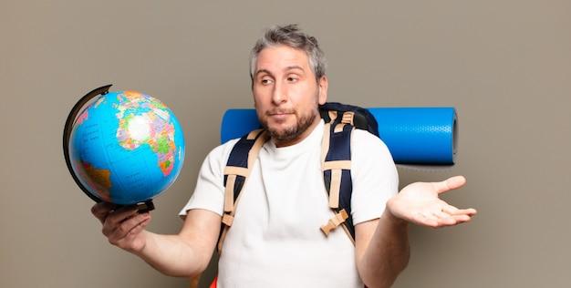 Podróżnik w średnim wieku z mapą świata