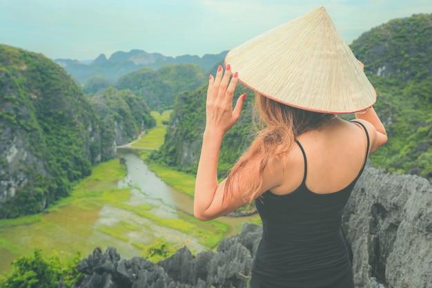 Podróżnik w wietnamie. młoda azjatykcia kobieta stoi na szczytowej jaskini mua. prowincja ninh binh, wietnam.