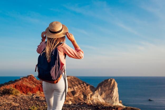 Podróżnik wycieczkuje biel plażą na morzu egejskim santorini wyspie, grecja cieszy się krajobraz. backpacker kobieta na wakacjach