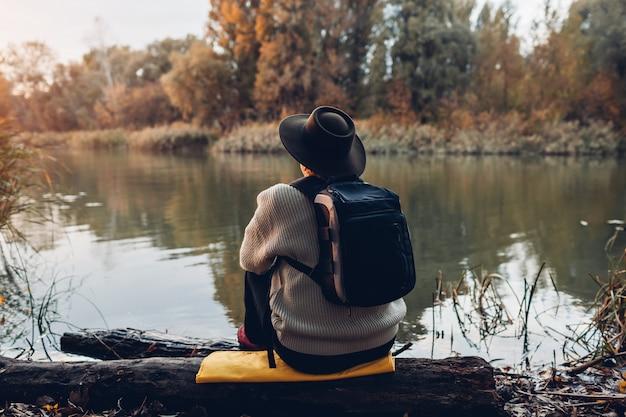 Podróżnik z plecaka obsiadaniem na brzeg rzeki przy zmierzchem. kobieta w średnim wieku, podziwiając jesień natura