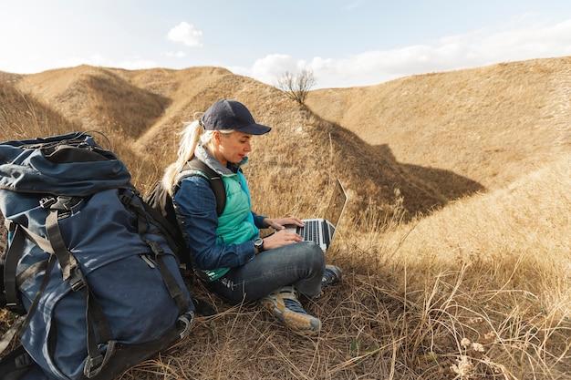 Podróżnik z plecakiem i laptopem na zewnątrz