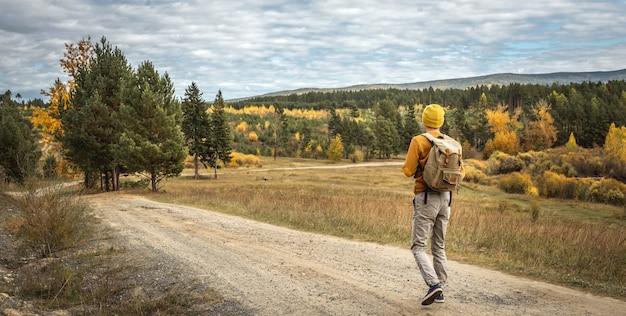 Podróżnik z plecakiem idzie pustą drogą wzdłuż lasu. pojęcie wolności, podróży, wędrówek i jesiennego nastroju