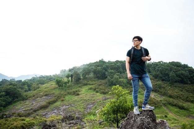 Podróżnik z plecakiem na wędrówki po górach. azjata stoi samotnie na szczycie góry