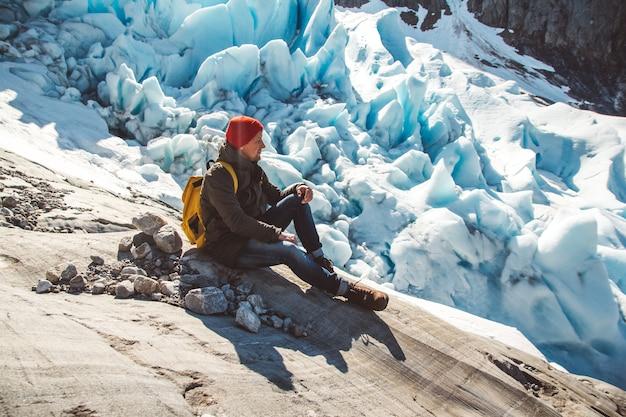 Podróżnik z plecakiem siedzący na skale na tle lodowca i śniegu