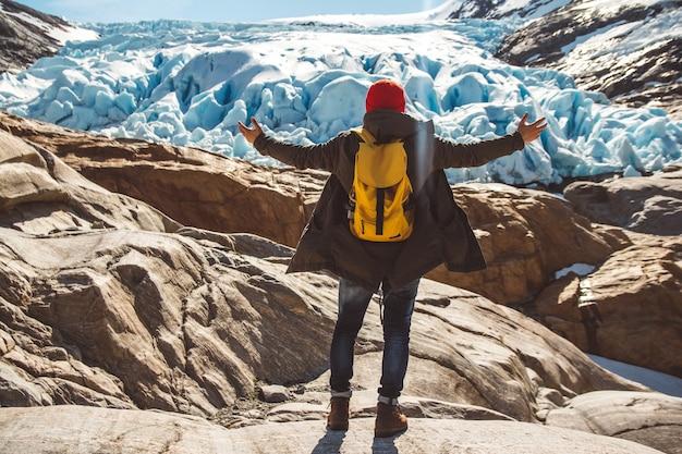 Podróżnik z plecakiem stojący na skale na tle gór i śniegu