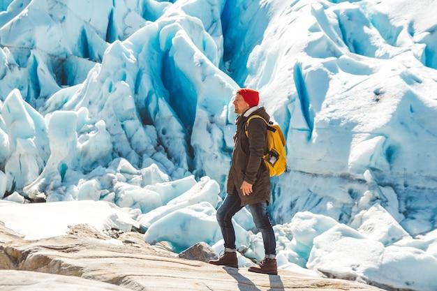 Podróżnik z plecakiem stojący na skale na tle lodowca góry i śnieg
