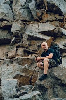 Podróżnik z plecakiem za ramionami siedzi na skale u podnóża wysokiego klifu.