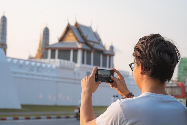 Podróżnika azjatycki mężczyzna używa telefon komórkowego dla bierze obrazek podczas gdy wydający wakacyjną wycieczkę przy bangkok, tajlandia