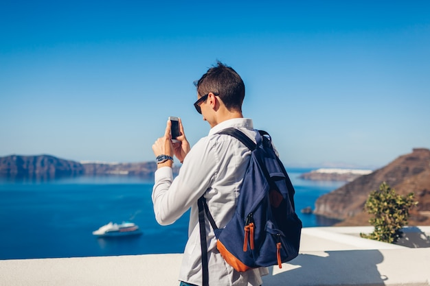 Podróżnika mężczyzna bierze fotografię z jego smartphone