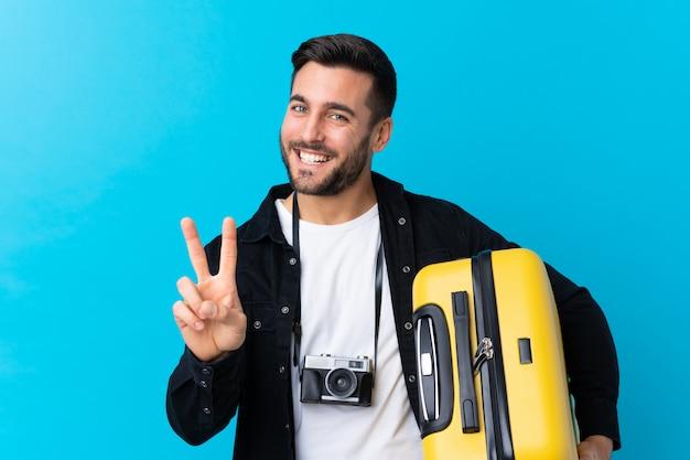 Podróżnika mężczyzna trzyma walizkę nad błękitem uśmiecha się zwycięstwo znaka i pokazuje