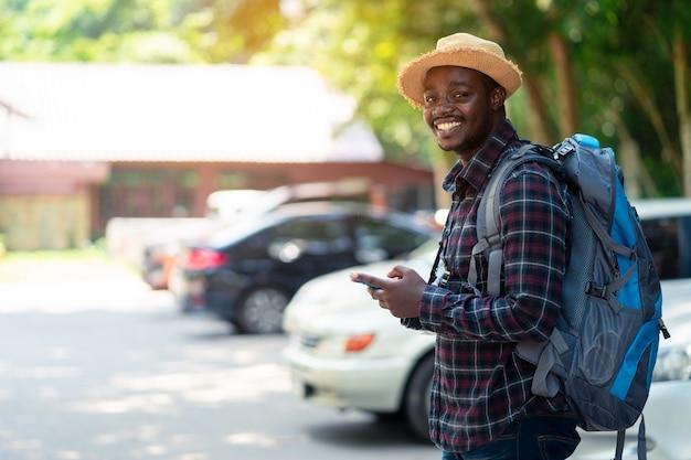 Podróżnika mężczyzna używa smartphone przy parking samochodowym i trzyma plecaka