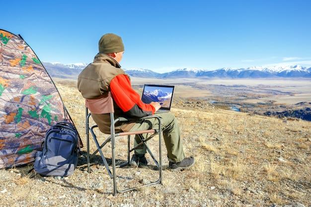 Podróżnika mężczyzna w górach z laptopem
