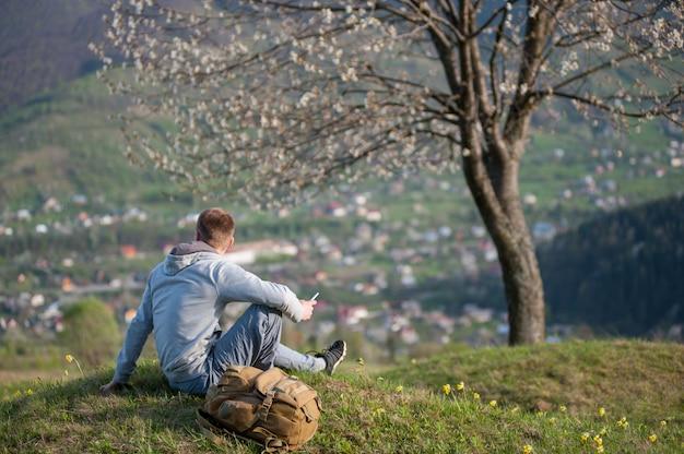 Podróżnika młody człowiek z plecakiem na wzgórzu