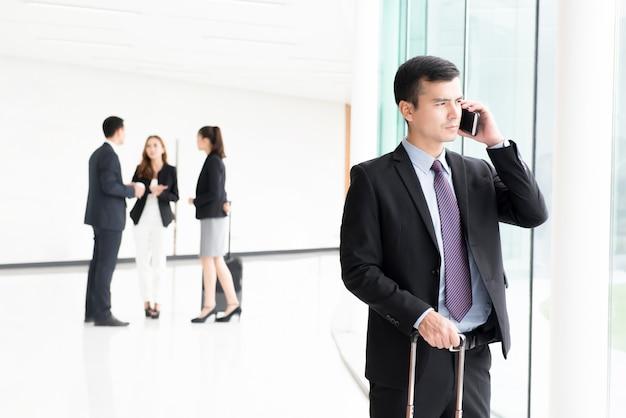 Podróżny biznesmen dzwoni na smartphone przy budynku korytarzem