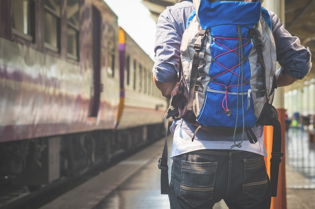 Podróżny człowiek czeka pociągiem na platformie kolejowej