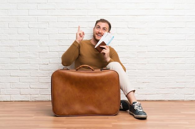 Podróżny mężczyzna z walizką i kartą pokładową, zamierzający zrealizować rozwiązanie, podnosząc palec w górę