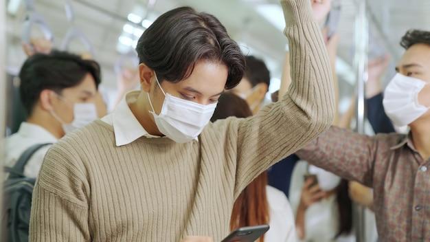 Podróżny nosi maskę na twarz podczas korzystania z telefonu komórkowego w pociągu publicznym