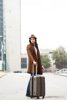 Podróżny w pełnym ujęciu z płaszczem i kapeluszem