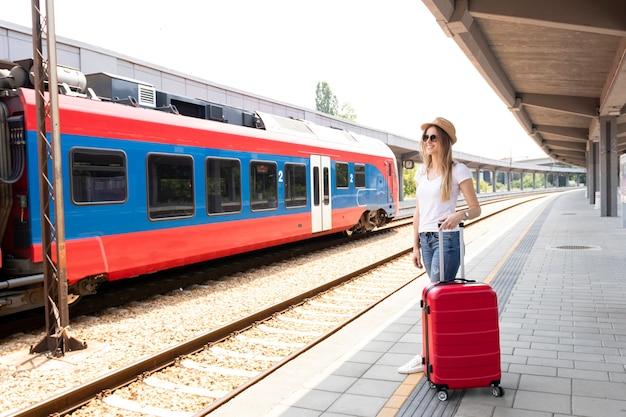 Podróżny z bagażem na dworcu kolejowym