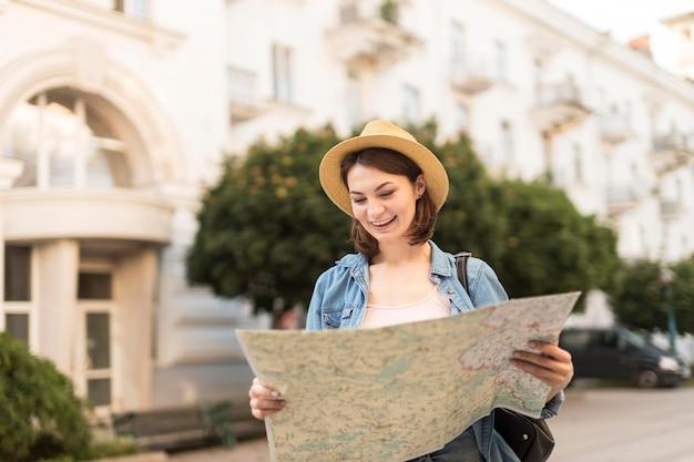 Podróżny z kapeluszem sprawdza lokalną mapę