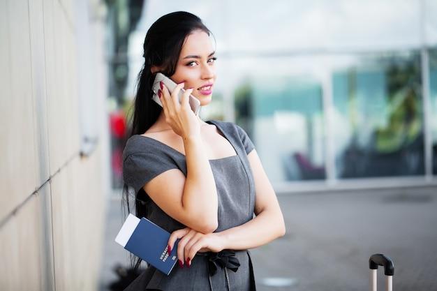 Podróżować. biznesowa kobieta opowiada na smartphone na lotnisku podczas gdy chodzący z ręka bagażem w lotnisku iść brama