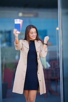 Podróżować. kobieta trzyma dwa lotniczy bilet w zagranicznym paszporcie blisko lotniska