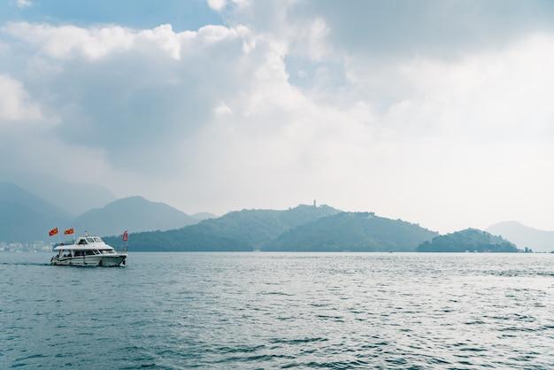 Podróżować łodzie pływające nad sun moon lake z górą w tle w yuchi township, nantou county, tajwan.