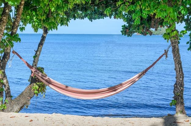Podróżować pojęcie: pusty hamak między drzewami na tropikalnej plaży.