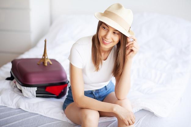 Podróżować. szczęśliwa kobieta pakuje walizkę w domu