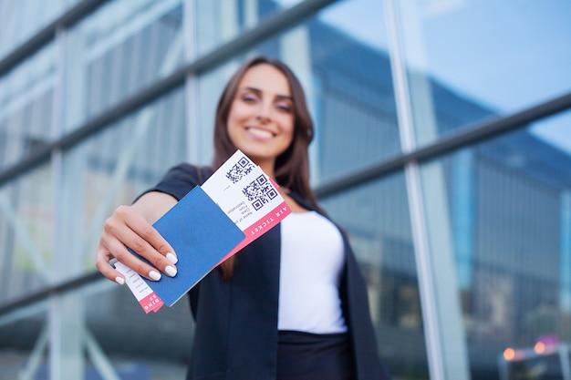 Podróżować. wesoła młoda kobieta trzyma bilety lotnicze na zewnątrz