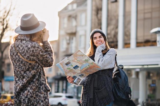 Podróżowanie po słonecznym wielkim mieście modnych wesołych dziewczyn. robienie zdjęć, cieszenie się wakacjami, podróżowanie z plecakiem, mapa miasta. pokazywanie prawdziwych pozytywnych, radosnych emocji, stylowy wygląd, pozowanie do kamery.