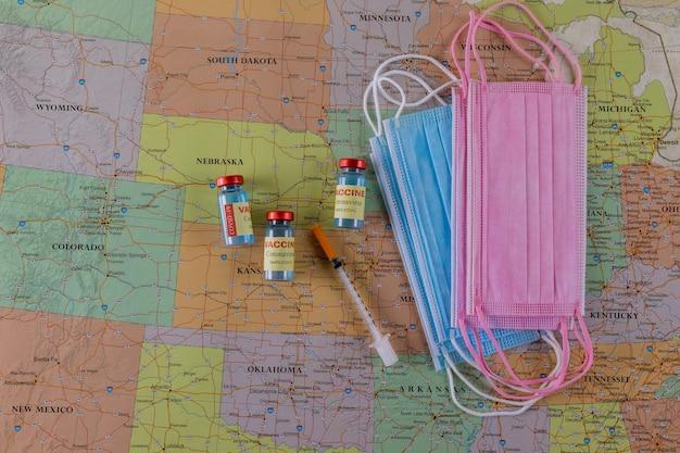 Podróżowanie po szczepieniu w butelce ze szczepionką, strzykawka z podróżą podczas maski medycznej chroniącej przed pandemią covid-19 na mapie ameryki północnej