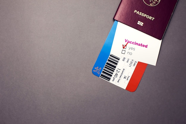 """Podróżowanie podczas pandemii covid-19, paszport z biletem lotniczym, zaszczepiona karta covid-19 ze znakiem """"tak"""" na szarym tle, koncepcja kontroli bezpieczeństwa i higieny pracy na lotnisku"""