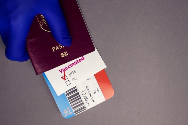 """Podróżowanie podczas pandemii covid-19, ręka trzymająca paszport z biletem lotniczym, zaszczepiona karta covid-19 ze znakiem """"tak"""" na szarym tle, koncepcja kontroli bezpieczeństwa i higieny pracy na lotnisku"""