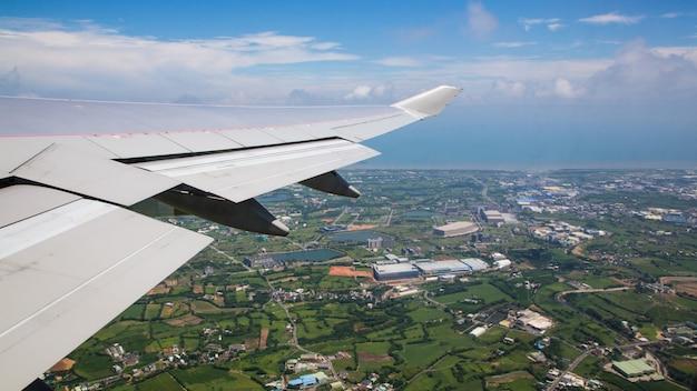 Podróżowanie samolotem. widok z lotu ptaka miasta na wyspie tajwan. zobacz skrzydło samolotu i miasto taoyuan w tle widziane przez okno samolotu podczas lotu.