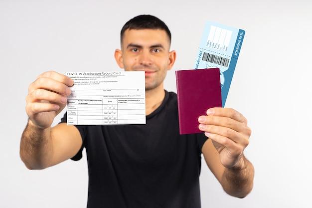 Podróżuj bezpiecznie podczas pandemii koronawirusa młody mężczyzna trzymający kartę szczepień na koronawirusa