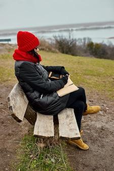 Podróżuj kobieta w czerwonym kapeluszu w czarnej kurtce pisz na notebooku, rób notatki
