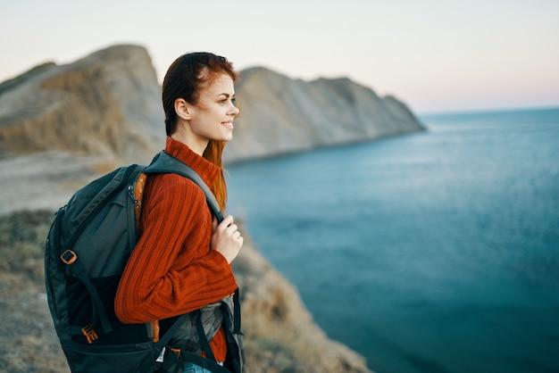 Podróżuj kobiety w swetrze plecak z tyłu krajobraz gór oceanu
