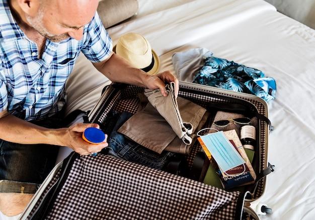Podróżuj nowym, normalnym, mężczyzna pakujący walizkę