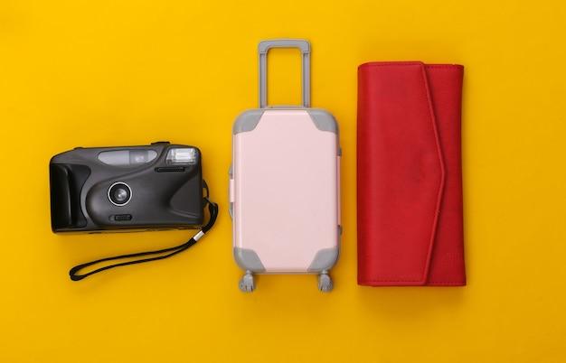 Podróżuj płasko. mini walizka podróżna z tworzywa sztucznego, czerwony portfel i aparat na żółtym tle. minimalistyczny styl. widok z góry