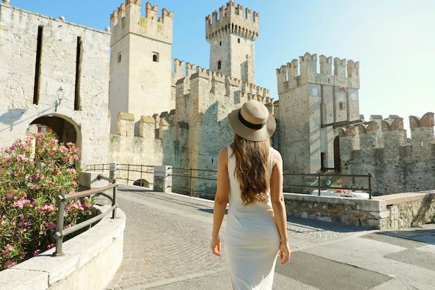 Podróżuj po włoszech. widok kobiety turystki idącej w sirmione w kierunku zamku scaligero z tyłu. widok z tyłu dziewczyny korzystających z wizyty w europie.