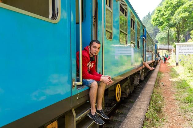 Podróżuj pociągiem po sri lance. bardzo wolny pociąg bez drzwi. malownicze miejsca na wyspie.