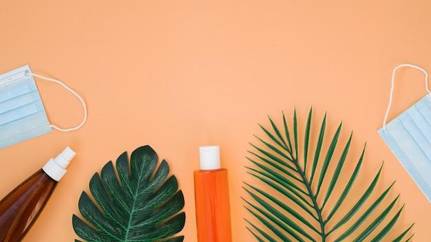 Podróżuj podczas koronawirusa. kremy do opalania, liście palmowe i maseczki lecznicze. miejsce na tekst