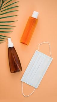 Podróżuj podczas koronawirusa. kremy do opalania, liście palmowe i maska medyczna.